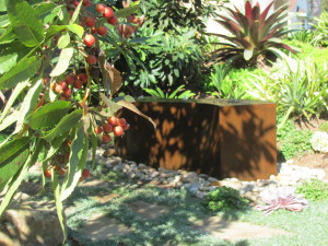 A naturally rusted cor-ten steel fountain in the front garden